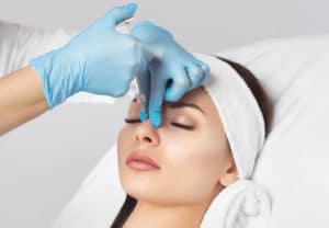 The doctor cosmetologist makes prick in the nose to correct the hump of a beautiful woman